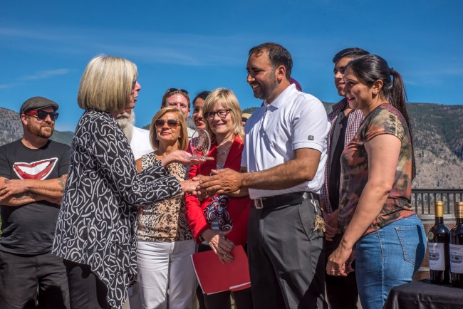 B.C. Lieutenant Governor Judith Guichon congratulates Mohan Gill, the owner of Bordertown Vineyards & Estate Winery, and members of his staff and family last Friday afternoon. Bordertown's 2013 Living Desert Red was one of 14 awards captured by wineries in the Okanagan Valley as part of the annual Lieutenant Governor wine awards. (Richard McGuire photo)